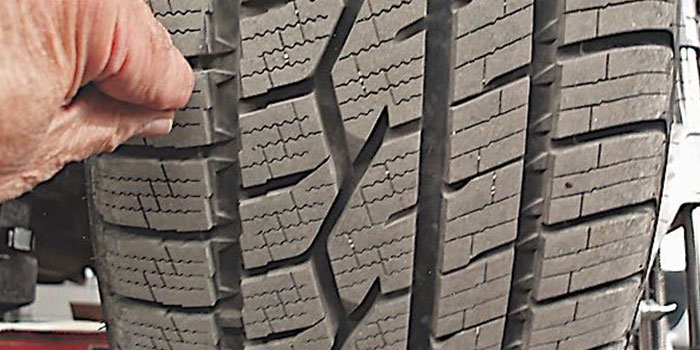 "Photo 1: Due to ""camber roll"" occurring during sharp turns, unusual tire wear problems will appear on the tire's outside tread bars. This tire is nearly new and is wearing in a normal pattern."